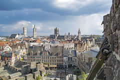 Gent, old town in Belgium. Cityscape in old town Gent of Belgium, belfry and St Bavo cathedral view through arrowslit from Gravensteen castle Royalty Free Stock Image