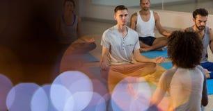 Gente adatta che si esercita nella classe di yoga Immagine Stock