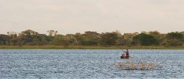 Gente africana che attraversa un lago in canoa di riparo Immagini Stock
