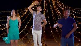 Gente alegre que baila en el partido de la playa de la noche metrajes