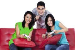 Gente alegre que juega a juegos con la palanca de mando Imagen de archivo