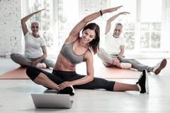 Gente allegra che prepara e che guarda allenamento online Fotografia Stock