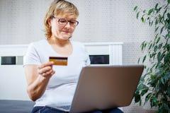 Gente anziana e concetto moderno di tecnologia Il ritratto di un 50s matura la carta di credito della tenuta della mano della don Fotografie Stock