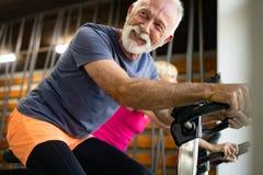 Gente apta madura biking en el gimnasio, ejercitando las piernas que hacen las bicis de ciclo del entrenamiento cardiio imagen de archivo