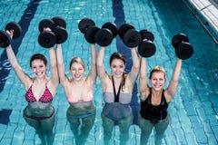 Gente apta que hace una clase de aeróbicos de la aguamarina Imagen de archivo