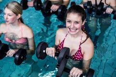 Gente apta que hace una clase de aeróbicos de la aguamarina Fotos de archivo