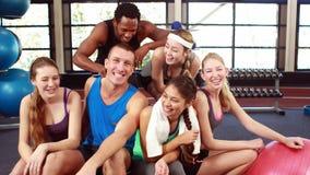 Gente apta que sonríe en la cámara en gimnasio almacen de metraje de vídeo