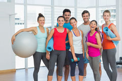 Gente apta que sonríe en una sala de ejercicio brillante Foto de archivo