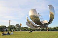Gente argentina que descansa en el parque con la escultura grande de la flor Foto de archivo libre de regalías