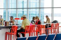 Gente asentada en la barra del restaurante en un aeropuerto Imagen de archivo libre de regalías