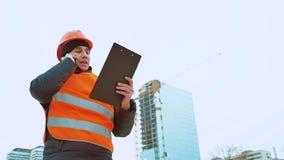 Gente asesor del hombre de la ingeniería en modelo de la tenencia del emplazamiento de la obra en su mano Inspector de construcci almacen de video