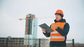 Gente asesor del hombre de la ingeniería en modelo de la tenencia del emplazamiento de la obra en su mano Inspector de construcci metrajes