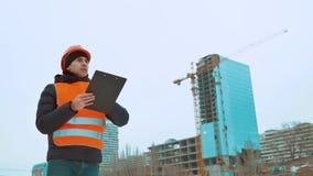Gente asesor del hombre de la ingeniería en modelo de la tenencia del emplazamiento de la obra en su mano Inspector de construcci almacen de metraje de vídeo