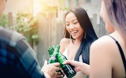 Gente asiática joven que lleva a cabo las botellas de cerveza y tintineo con la consumición imagen de archivo