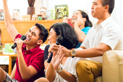 Gente asiática que canta en el partido del Karaoke Imagenes de archivo
