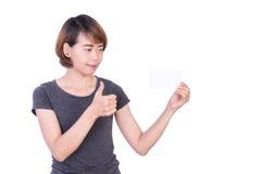 Gente asiatica: Bella giovane signora astuta che mostra i pollici su e sembrare carta in bianco a disposizione su fondo bianco Fotografie Stock Libere da Diritti
