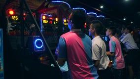 Gente asiatica che gioca pallacanestro e che getta palla ad Arcade Machine nel centro commerciale di zona MBK del gioco 4K bangko archivi video