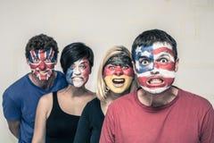 Gente asustadiza con las banderas en caras Imagenes de archivo