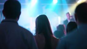 Gente atractiva joven que baila en un club nocturno durante un funcionamiento en una etapa Muchachas y muchachos que cuelgan haci almacen de metraje de vídeo
