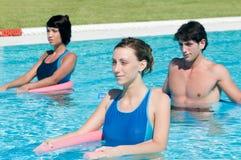 Gente attiva che fa ginnastica del aqua in un raggruppamento Fotografie Stock