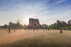 Gente birmana che gioca a calcio sul campo con le rovine antiche della pagoda nei precedenti durante il tramonto immagine stock libera da diritti