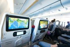 Gente a bordo que mira monitores del asiento. Foto de archivo
