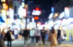 Gente borrosa que camina en vida nocturna de la ciudad de la calle de las compras Imagen de archivo