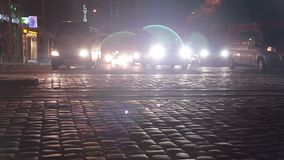 Gente borrosa que cruza la calle en la ciudad en la noche con los coches, el semáforo y los edificios como fondo, noche almacen de video
