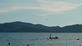 Gente borrosa que juega la agua de mar con felicidad almacen de metraje de vídeo