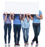 Gente casual que oculta sus caras detrás de una bandera en blanco Imagenes de archivo
