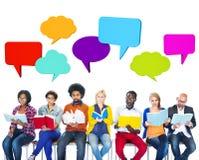Gente colorida multiétnica que lee con las burbujas del discurso Foto de archivo libre de regalías