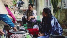 Gente comprar y vender los mariscos y la verdura en el mercado de la comida de la calle en Asia almacen de video