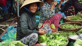 Gente comprar y vender los mariscos y la verdura en el mercado de la comida de la calle en Asia metrajes