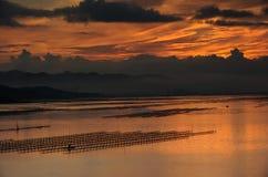 Gente con el barco de fila en el mar en la salida del sol Imágenes de archivo libres de regalías