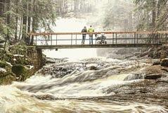 Gente con el bebé en el puente estirado sobre el río de la montaña de la inundación fotos de archivo