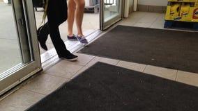 Gente con el carro de la compra que camina a través de las puertas almacen de metraje de vídeo