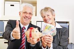 Gente con el dinero y la hucha Imagenes de archivo