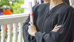 Gente con el diploma negro del control de los vestidos de la graduación Imágenes de archivo libres de regalías