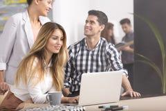 Gente con el ordenador portátil que disfruta de trabajo en equipo fotos de archivo libres de regalías