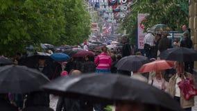 Gente con el paseo de los paraguas debajo de la lluvia 4 almacen de video