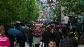 Gente con el paseo de los paraguas debajo de la lluvia 2 almacen de metraje de vídeo