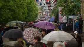 Gente con el paseo de los paraguas debajo de la lluvia 7 metrajes