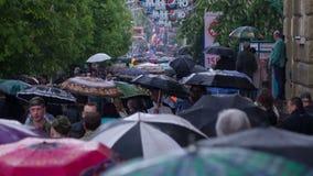 Gente con el paseo de los paraguas debajo de la lluvia 6 almacen de video