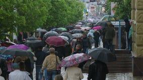 Gente con el paseo de los paraguas debajo de la lluvia 3 almacen de metraje de vídeo
