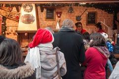 Gente con el sombrero de la Navidad en el mercado de la Navidad Fotografía de archivo