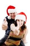 Gente con el sombrero de la Navidad que muestra los pulgares para arriba Foto de archivo