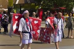 Gente con hola las banderas del gatito en el vestido blanco en el desfile tradicional japonés en la EXPO 2015 Foto de archivo libre de regalías