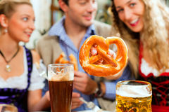 Gente con la cerveza y el pretzel en pub bávaro Foto de archivo