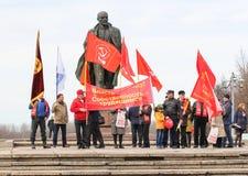 Gente con las banderas del día de fiesta en el monumento a Lenin Foto de archivo libre de regalías