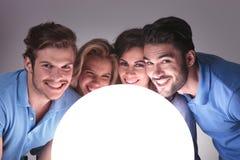 Gente con las caras cerca de una bola grande de la luz Imagen de archivo libre de regalías